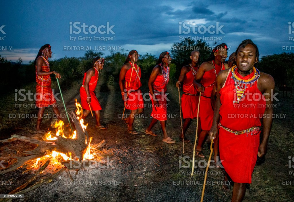 Warriors the Masai tribe dancing ritual dance around the fire late in the evening. stock photo