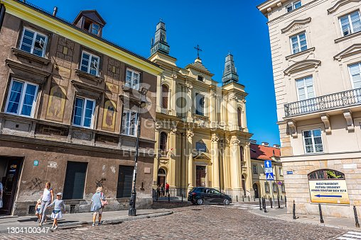 Warsaw, Poland - August 22, 2018: New town historic road during sunny summer day with The Franciscans Friars catholic church of St. Francis at Zakroczynska street