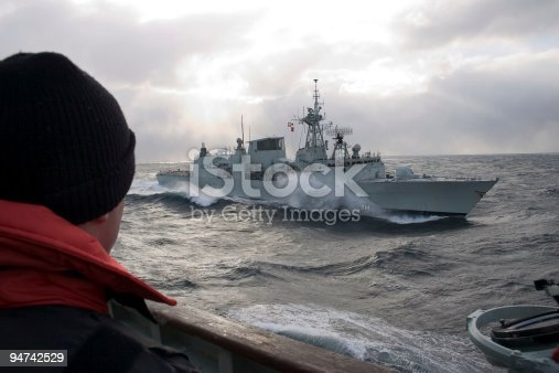 Modern frigate slicing through the waves.
