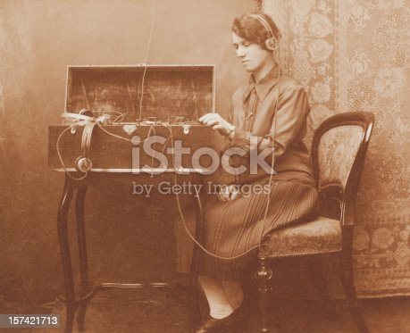 Vintage Victorian sepia image of a woman using a morse code radio communications device housed within an oak box.