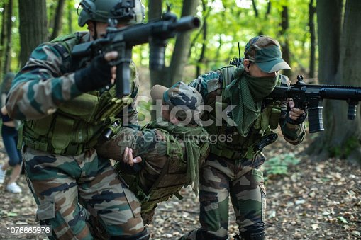 Two soldiers  Helping Injured Soldier In Action Of War In Wild Area