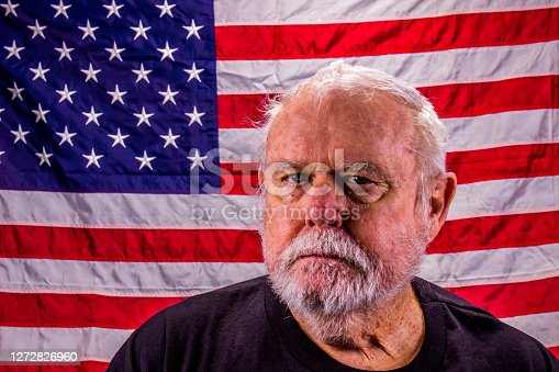 Old Wary Vietnam Veteran With Scraggly Beard In Front Of American Flag