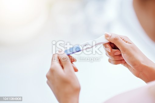 Cropped shot of a young woman taking a pregnancy test