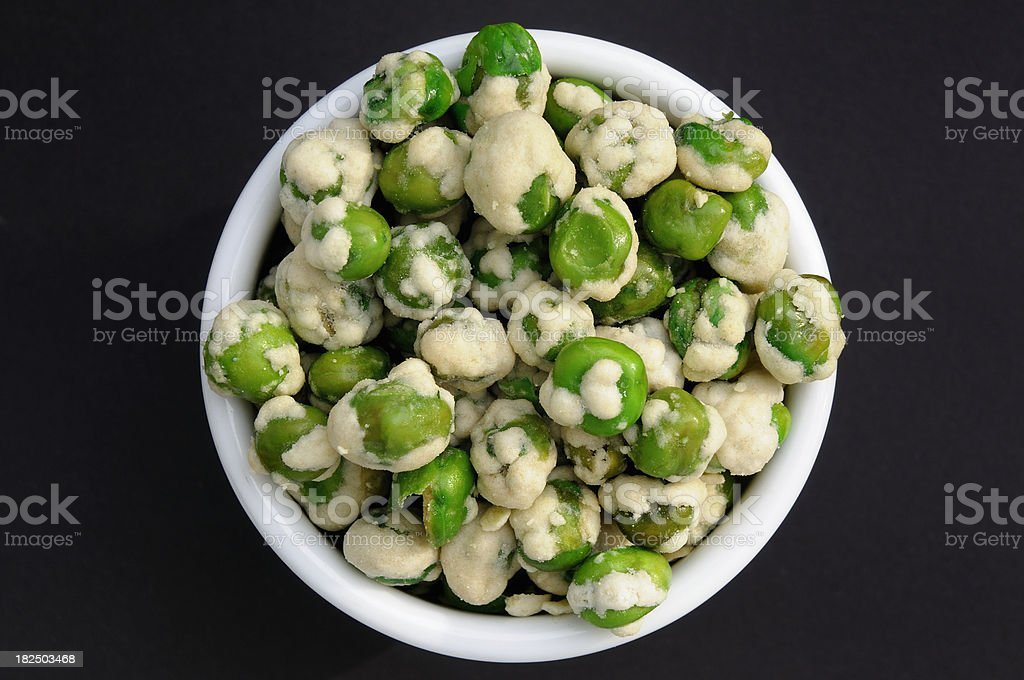 Wasabi coated peas in a white bowl stock photo