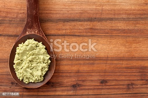 Top view of wooden spoon over table with wasabi paste on it