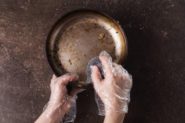 tvätta stek pannan på en mörk marmor bakgrund. hygien. tvätta rätter med handskar - frying pan bildbanksfoton och bilder