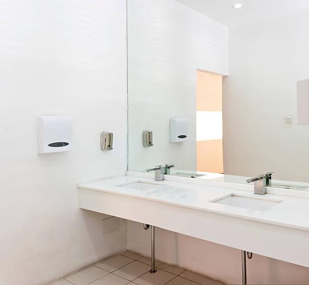 Wasserhähne, Waschbecken und Spiegel in eine öffentliche Toilette – Foto