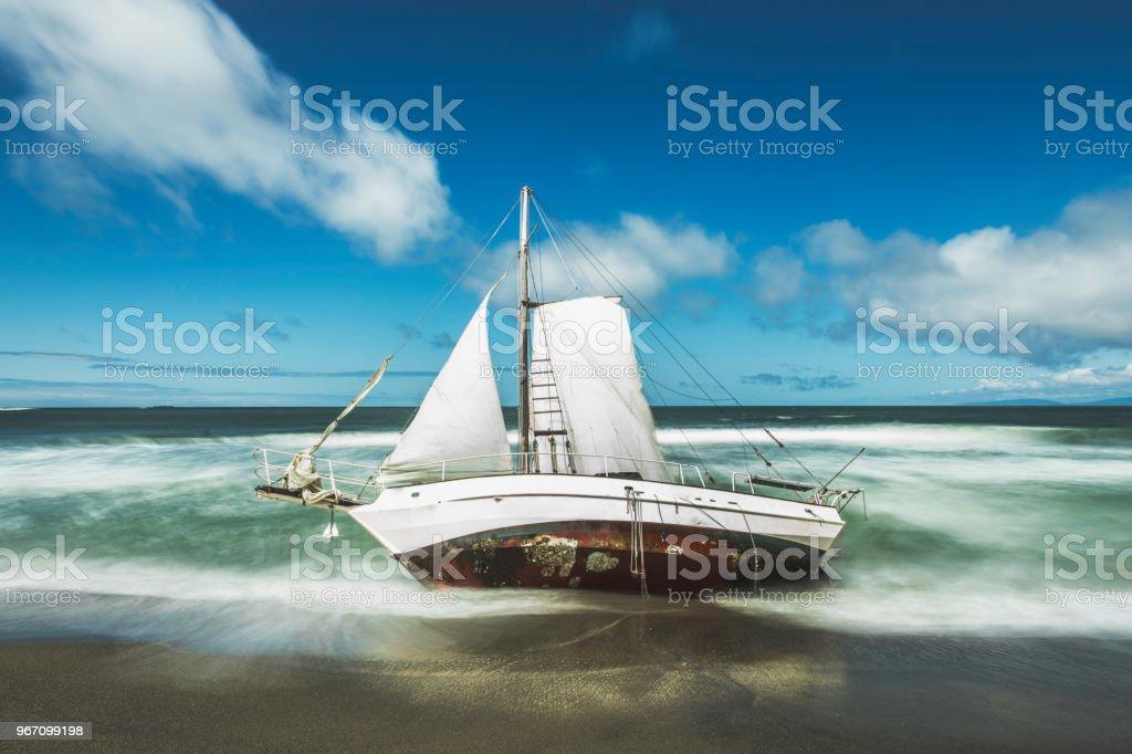 Washed Ashore Sailboat on Beach stock photo