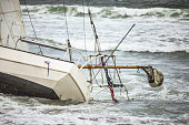 High quality stock image of a shipwrecked sailboat washed ashore in Pacifica, Ca
