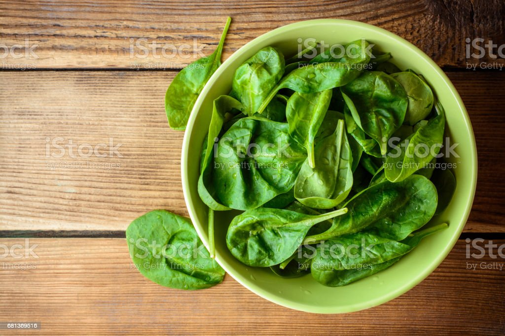 Washed fresh spinach leaves in bowl on rustic wooden table. stock photo