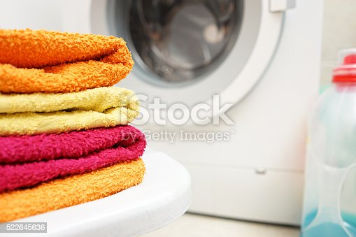 1164403372 istock photo washed towels stacked with washing machine in background 522645636