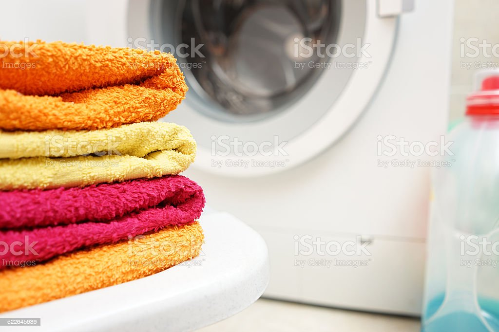 washed towels stacked with washing machine in background stock photo