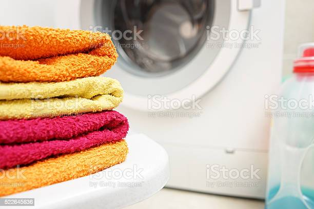 Washed Towels Stacked With Washing Machine In Background Stock Photo - Download Image Now