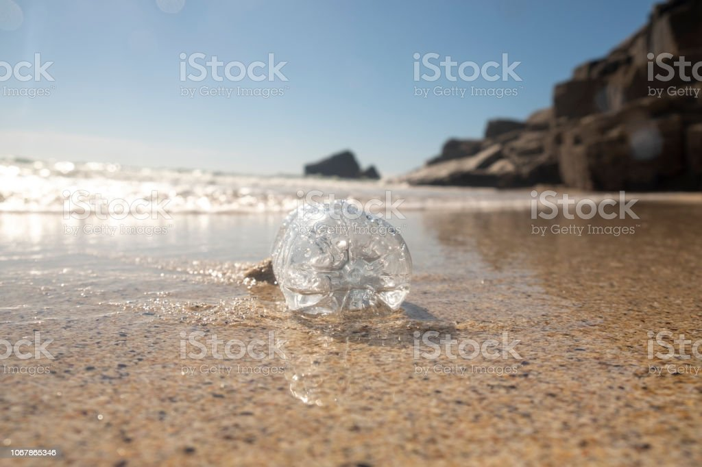 Washed up plastic bottle on a bright sunny day. stock photo