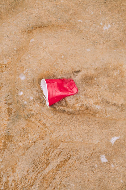 washed up plastic cup on the shoreline of a beach. - trash stock pictures, royalty-free photos & images