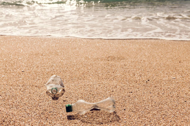 washed up used plastic bottle on a beach. - trash stock photos and pictures