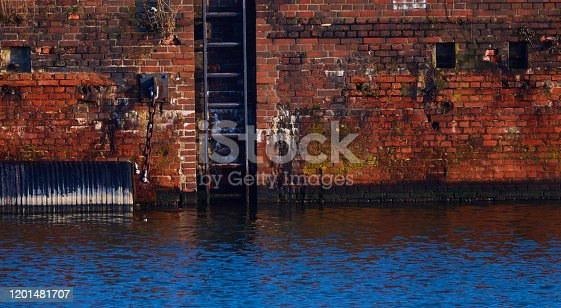 Washed-out and weathered red quay wall made of tile stones with an iron ladder in the blue water of the harbour