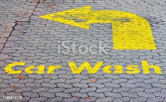 istock Washed-out old ugly painted yellow entry sign for a car wash on a dirty old pavement of a petrol station 1185874175