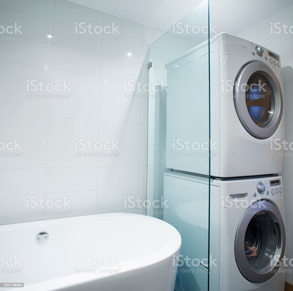 Washer and dryer stacked on each other in bathroom stock photo