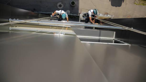 Washers Wash the Windows of Modern Skyscraper stock photo