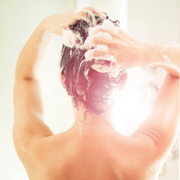 Washing a hair Mid adult woman washing a hair at domestic bathroom wet hair stock pictures, royalty-free photos & images