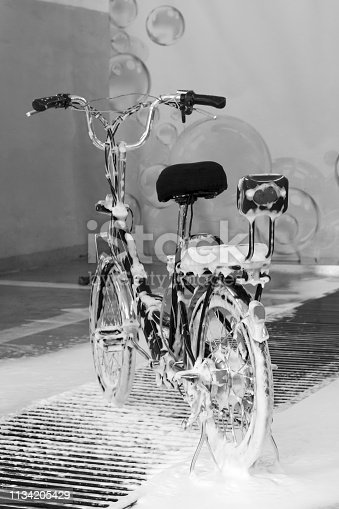 Washing an electric bicycle with a jet of foam in a car wash. Black and white image