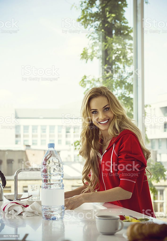 Washing dishes Young woman washing dishes in modern kitchen, smiling at the camera. 20-24 Years Stock Photo