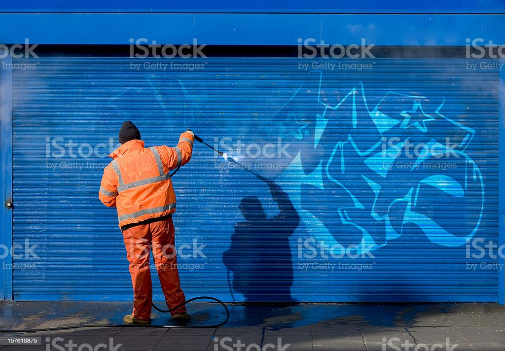 Washing graffiti off a security grill. royalty-free stock photo