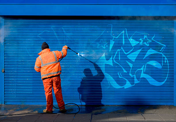 Washing graffiti off a security grill. stock photo