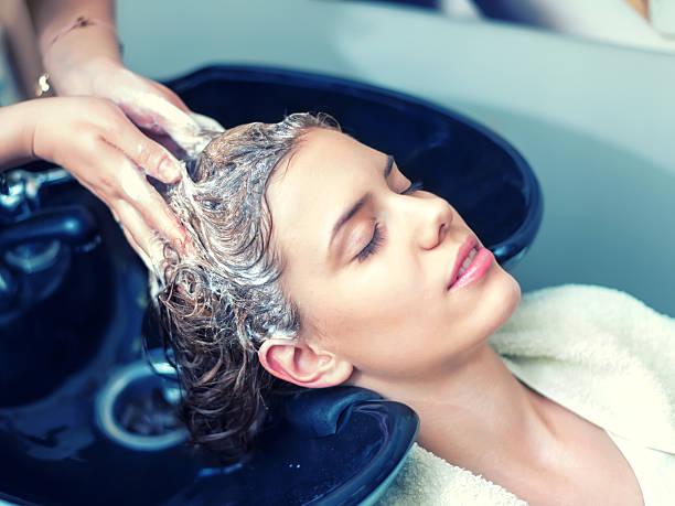 washing hair in hair salon - bacinella metallica foto e immagini stock