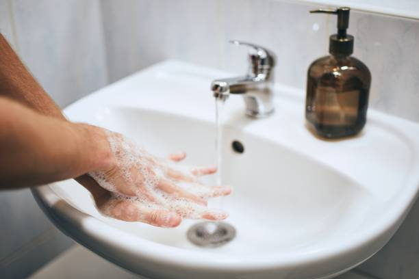 Washing hands at home in bathroom stock photo