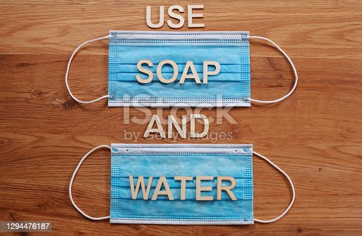 'USE SOAP AND WATER' written with wooden letters on a blue surgical face mask. COVID-19 coronavirus pandemic. Directly above, looking down.