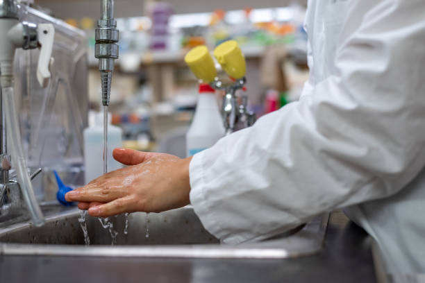 Washing hands in biomedical research laboratory with biohazards stock photo
