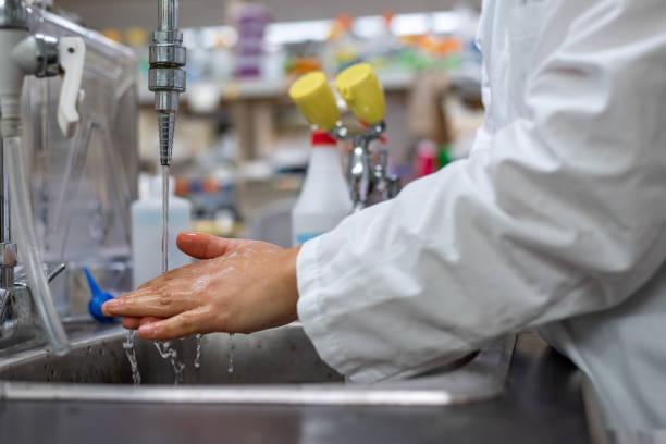 laver les mains dans le laboratoire de recherche biomédicale avec risques biologiques - technique photographique photos et images de collection