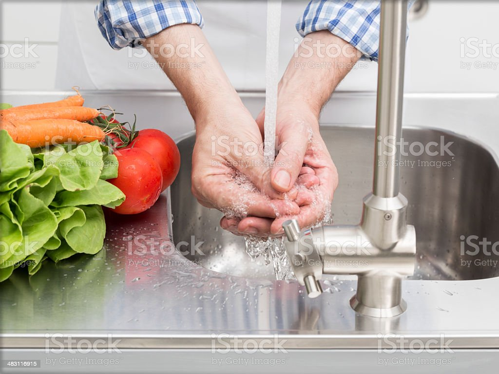 Washing hands in kitchen stock photo