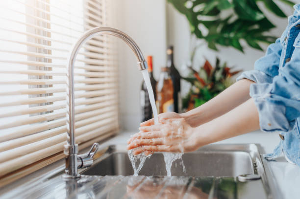 washing hands in sink before cooking at home stock photo