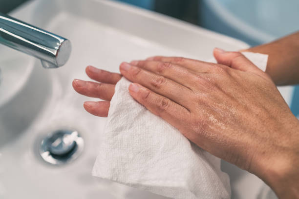 Washing hands steps for personal hygiene COVID-19 prevention drying hand with paper towel after handwash. Coronavirus infection preventive cleaning stock photo