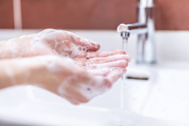 Washing hands with water and liquid soap in the bathroom. Hygiene anti-virus concept stock photo