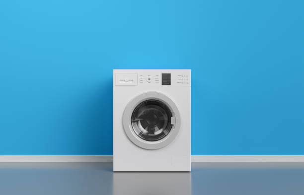 Washing machine at blue wall, frontal view with copy space,3d rendering (general design and captions) Washing machine at blue wall, frontal view with copy space,3d rendering (general design and captions) machinery stock pictures, royalty-free photos & images