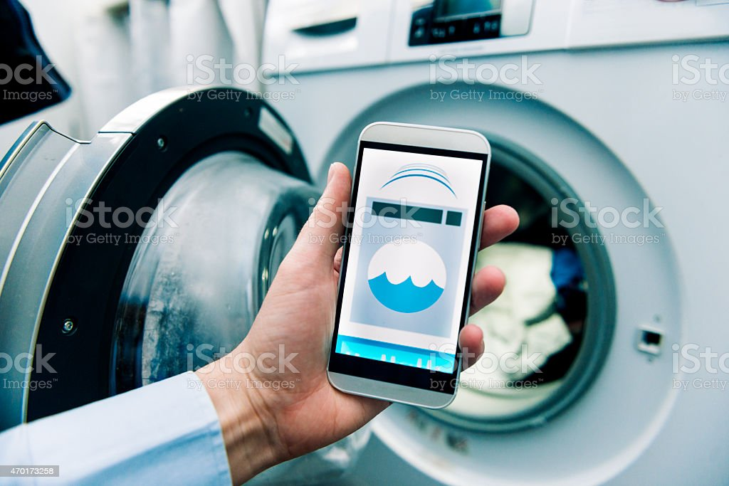 Washing machine controlled by app on a smart phone stock photo