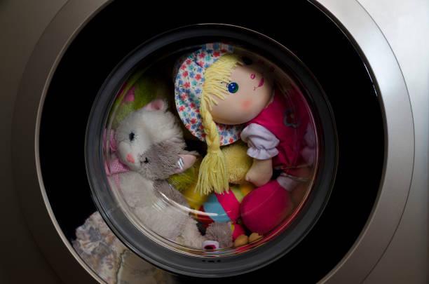 Washing machine door with rotating toys inside stock photo