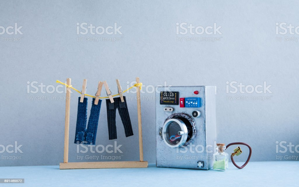 Washing machine laundry concept, men's jeans pants dried on clothesline with clothespins. Gray wall interior, blue floor. Funny toys creative design stock photo