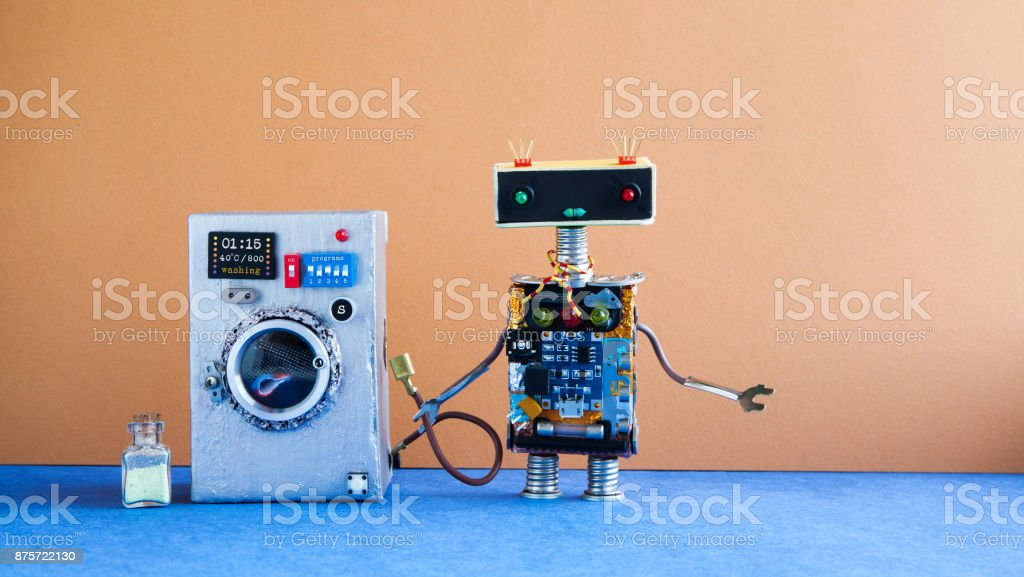 Washing machine laundry concept. Robot house master on brown wall interior, blue floor. Funny toys creative design stock photo