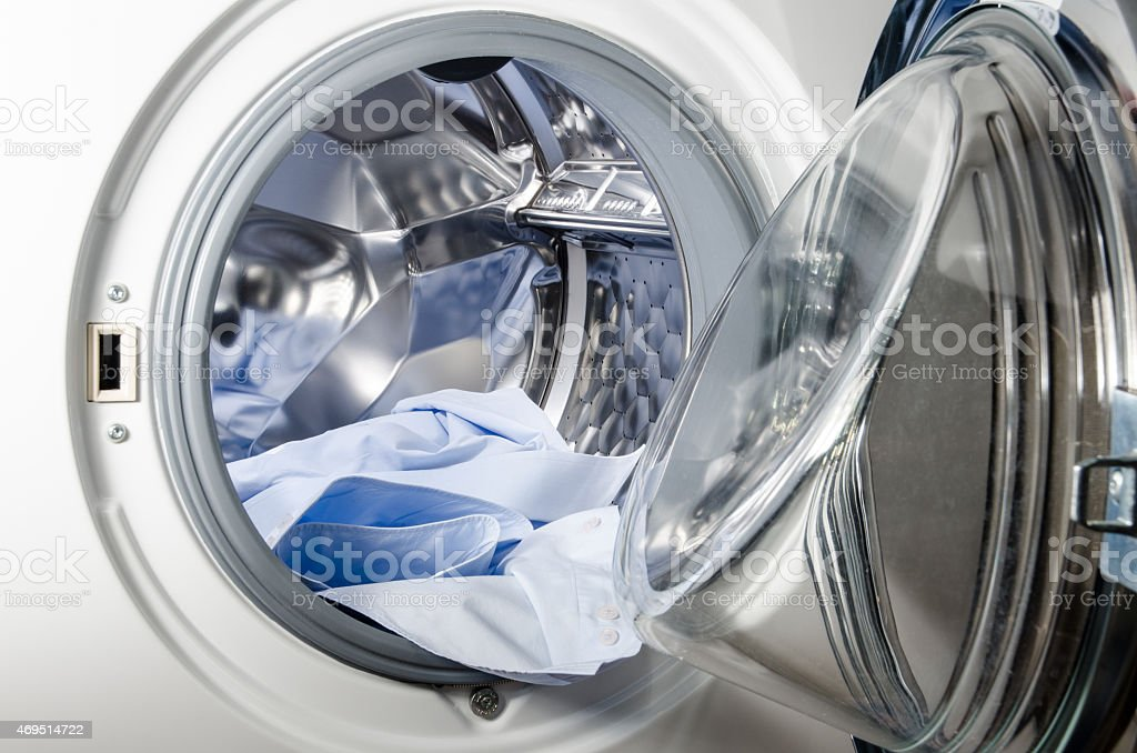 washing machine loaded with blue shirt stock photo
