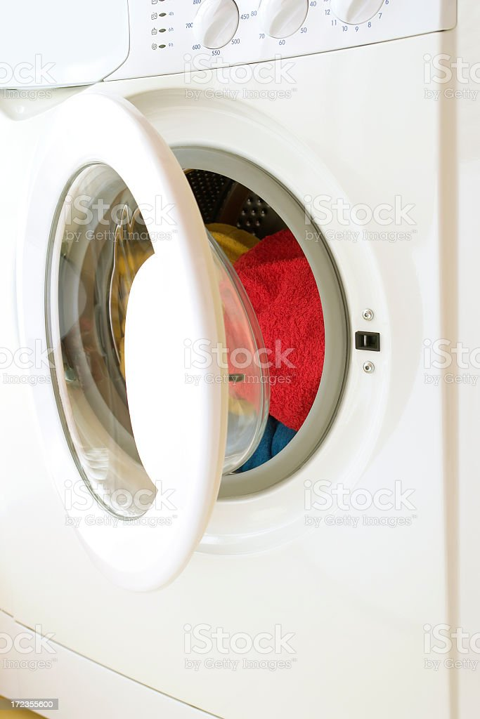 Washing machine, opened door, laundry inside, three colorful towels royalty-free stock photo