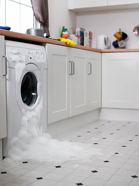 Washing machine overflowing in kitchen stock photo