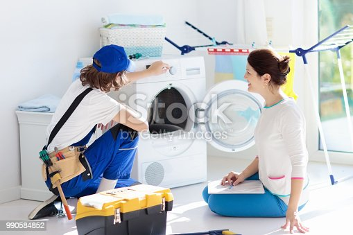 istock Washing machine repair technician. Washer service. 990584852
