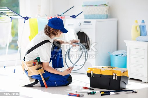 istock Washing machine repair technician. Washer service 990598894