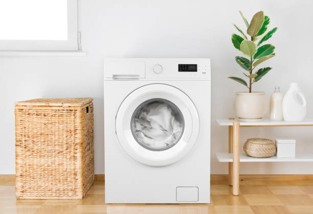 Washing machine with clothes in modern bathroom interior stock photo