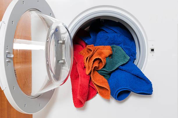 Washing machine with colored laundry stock photo
